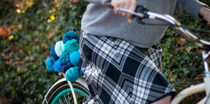 A girl riding a bike laden with blue yarn