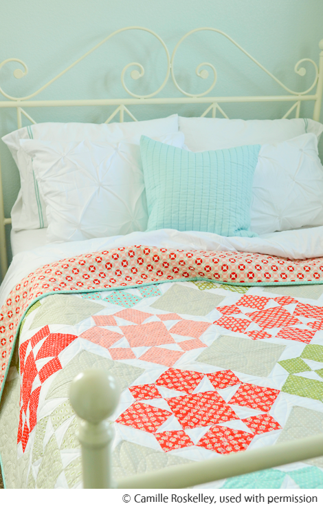 Camille Roskelley's image of a quilt on a green bed